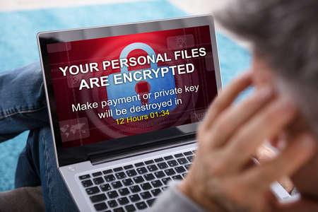Nahaufnahme einer Person, die Laptop-Bildschirm betrachtet, der verschlüsselten Text der persönlichen Dateien zeigt