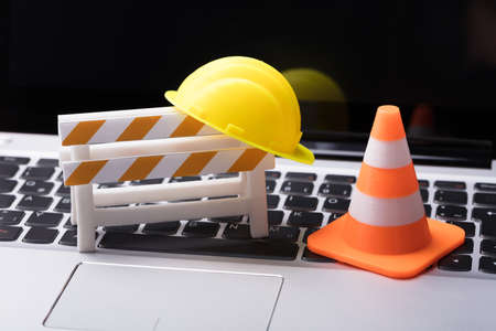 Road Barrier With Hard Hat And Traffic Cone On Laptop Keypad 免版税图像 - 97150786