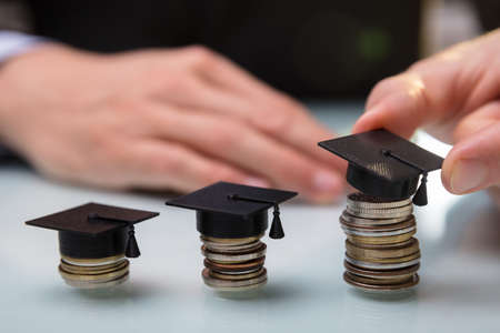 Close-up Of A Businesspersons Hand Placing Graduation Hat Over Stacked Coins In A Row