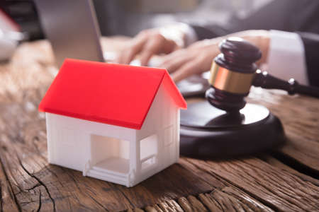 Close-up Of House Model With Red Roof And Gavel On Wooden Desk In Courtroom