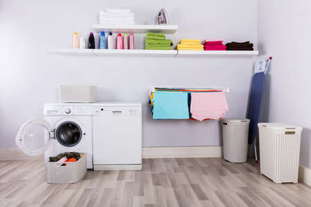 Basket Full Of Dirty Clothes In Front Of Washing Machine At Laundry Room