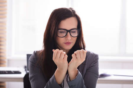 Close-up Of A Young Businesswoman Looking At Her Finger Nails In Office Stock Photo
