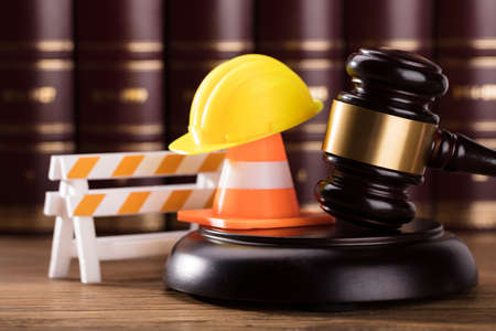 Close-up Of Mallet With Road Barrier, Yellow Hard Hat And Traffic Cone In Courtroom Foto de archivo