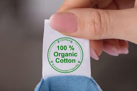 Close-up de la mano de una persona sosteniendo la etiqueta mostrando 100% algodón orgánico