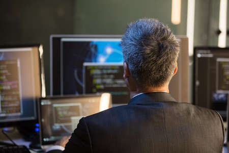 Rear View Of A Businessman Looking At Multiple Computer Screens In Office