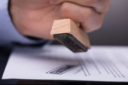 Close-up Of A Businessperson's Hand Stamping Document Stock Photo