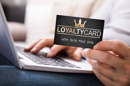 Close-up Of A Person's Hand With Loyalty Card Using Laptop Imagens