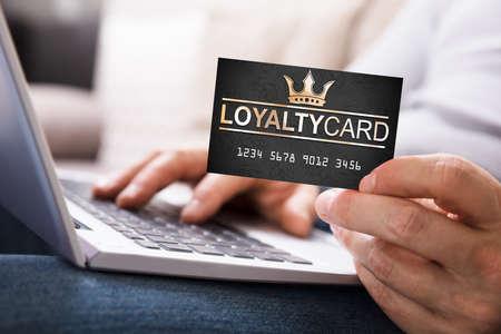 Gros plan de la main d'une personne avec carte de fidélité à l'aide d'un ordinateur portable Banque d'images
