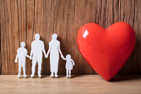 Close-up Of A Family Holding Hands Besides Red Heart Shape