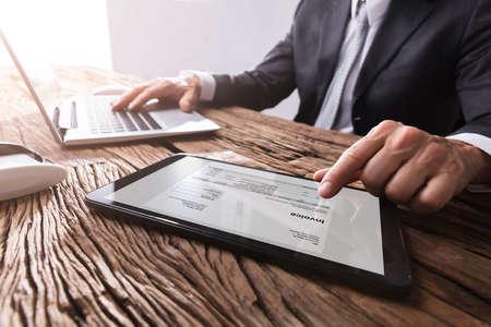 Nahaufnahme der Hand eines Geschäftsmannes, die mit Rechnung auf digitalem Tablett arbeitet