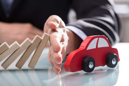 Close-up Of A Businesspersons Hand Stopping Wooden Blocks From Falling On Red Car Over Desk Standard-Bild