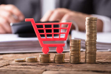 Close-up Of Red Shopping Cart On Stacked Golden Coins Over Wooden Desk Standard-Bild