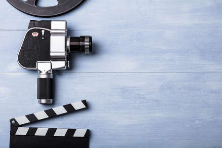 High Angle View Of Movie Camera With Film Reel And Clapper Board On Wooden Plank Standard-Bild
