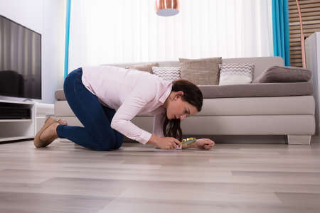 Side View Of A Young Woman Looking At Hardwood Floor Through Magnifying Glass 免版税图像