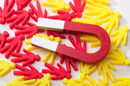 Close-up Of Horseshoe Magnet With Red And Yellow Human Figures On White Background