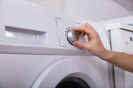 Close-up Of A Womans Hand Turning Button Of Washing Machine