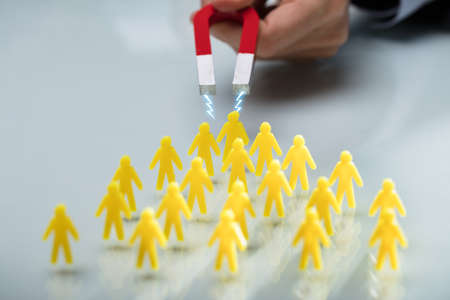 Hand Of A Person Attracting Group Of Yellow Figurines With Magnet On Reflective Desk