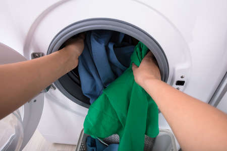 Close-up Of A Womans Hand Putting Clothes In Washing Machine Standard-Bild