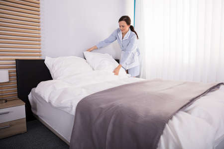 Happy Female Housekeeper Arranging Pillow On Bed In Hotel Room Archivio Fotografico