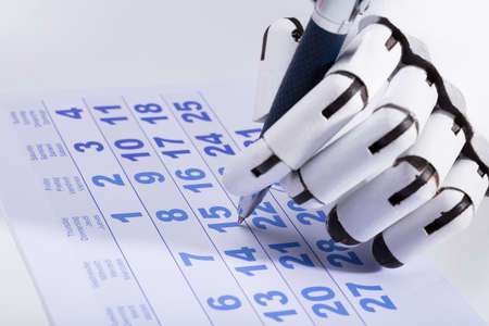 Close-up Of A Robotic Hand Marking Date On Calendar With Pen