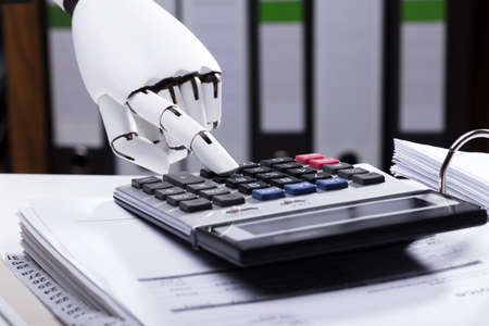Close-up Of A Robotic Hand Using Calculator Stockfoto