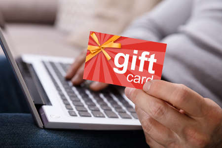 Close-up Of A Person's Hand Working On Laptop Holding Gift Card Foto de archivo