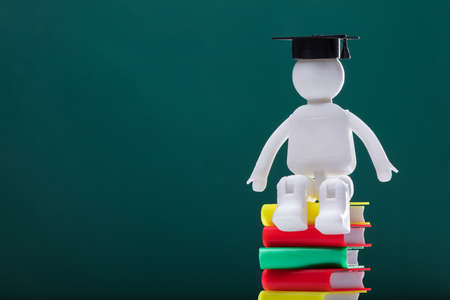 Human Figure With Graduation Hat Sitting On Multi Colored Stacked Books
