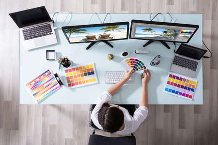 High Angle View Of A Female Designer Using Color Swatch While Working On Multiple Computer