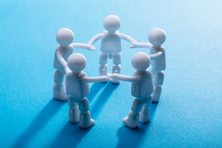 Close-up Of Human Figures Holding Their Hands Standing On Blue Background Stock Photo