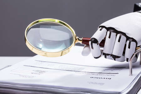 Close-up Of A Robotic Hand Holding Magnifying Glass Over Invoice At Workplace