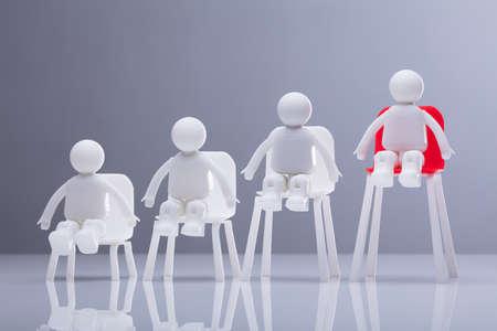 Close-up de figuras humanas sentadas en sillas blancas y rojas en aumento en una fila.
