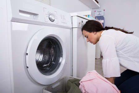 Exhausted Young Woman Besides Washing Machine And Basket Full Of Clothes In Laundry Room 写真素材