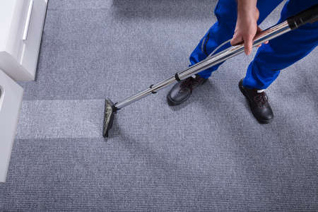 Janitors Hand Cleaning Carpet With Vacuum Cleaner