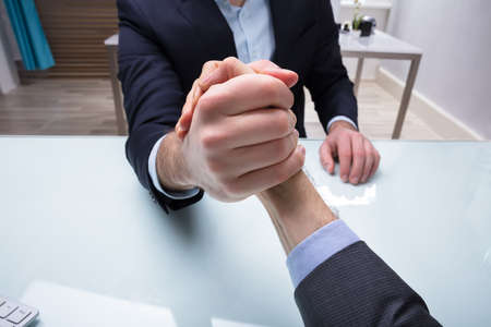Close-up Of Two Businessmen Competing In Arm Wrestling On Desk At Workplace 版權商用圖片