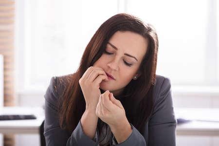 Close-up de una joven empresaria mordiéndose las uñas