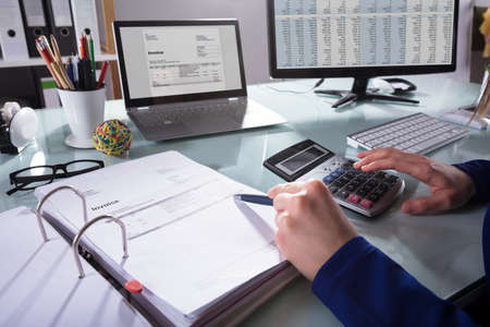 Close-up Of A Businesspersons Hand Calculating Invoice At Workplace