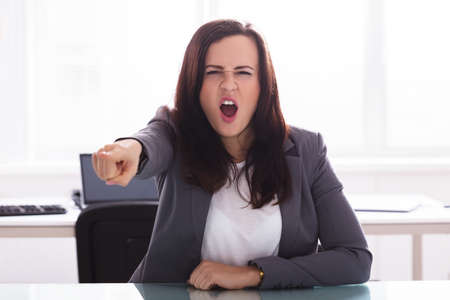 Angry Businesswoman Shouting And Pointing Finger In Office Foto de archivo