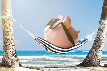 Pink Piggy Bank Wearing Sunglasses Relaxing On Hammock At The Beach