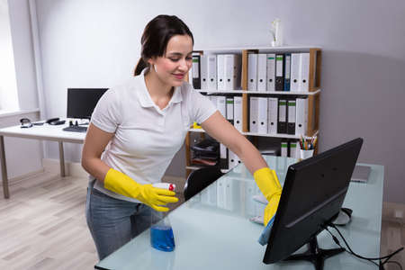 Young Female Janitor Cleaning Computer With Rag At Workplace
