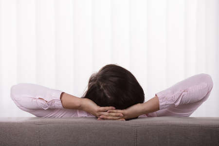 Close-up Of A Woman On Sofa With Hand Behind Head Stock Photo