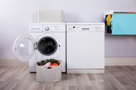 Empty Washing Machine With Pile Of Dirty Clothes In Basket At Laundry Room
