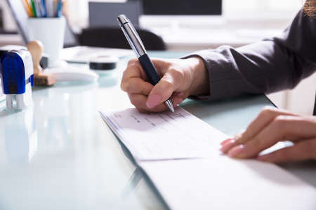 Close-up Of A Businessperson's Hand Signing Cheque With Pen In Office Archivio Fotografico