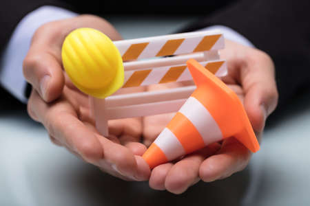 Close-up Of Persons Hand Holding Barricade With Traffic Cone And Hard Hat