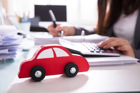 Close-up Of Red Wooden Car In Front Of Businessperson Calculating Bill Stock Photo