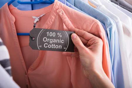 Primer plano de la mano de una mujer con etiqueta que muestra 100 por ciento de algodón orgánico Foto de archivo
