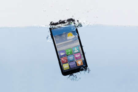 Close-up Of A New Black Mobile Phone Submerged In Water