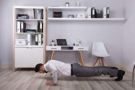 Young Businessman Doing Push Up At His Workplace
