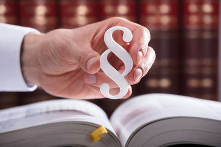 Close-up Of A Judges Hand Holding White Paragraph Symbol Stock Photo