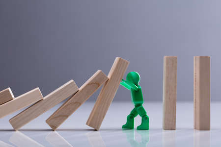 Side View Of A Green Human Figure Stopping Wooden Dominos Blocks Against Grey Background