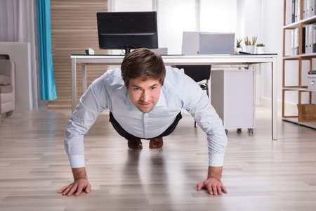 Side View Of A Young Businessman Doing Push Up In Office